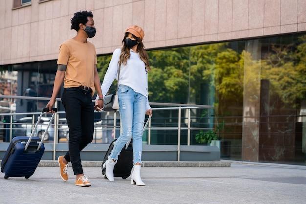 Portrait d'un jeune couple de touristes portant un masque de protection et portant une valise en marchant à l'extérieur dans la rue. notion de tourisme. nouveau concept de mode de vie normal.