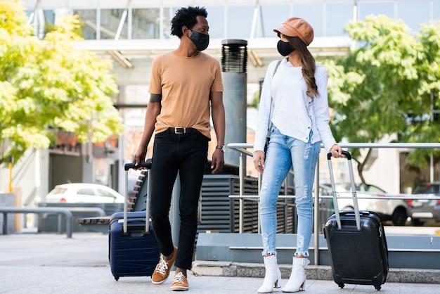 Portrait de jeune couple de touristes portant un masque de protection et portant une valise tout en marchant à l'extérieur dans la rue. concept de tourisme. nouveau concept de mode de vie normal.
