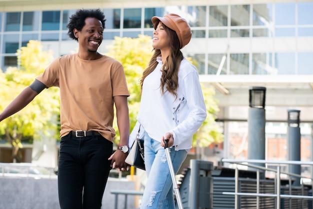 Portrait de jeune couple de touristes transportant une valise en marchant à l'extérieur dans la rue. concept de tourisme.