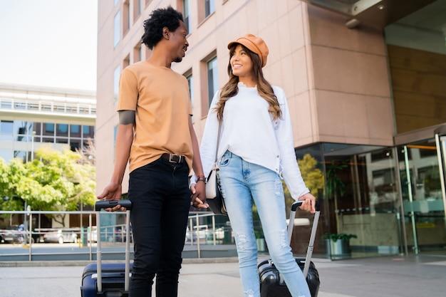 Portrait de jeune couple de touristes transportant une valise tout en marchant à l'extérieur dans la rue.