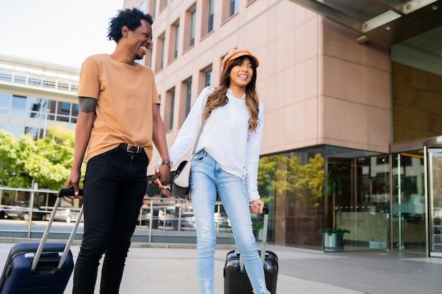 Portrait de jeune couple de touristes transportant une valise tout en marchant à l'extérieur dans la rue