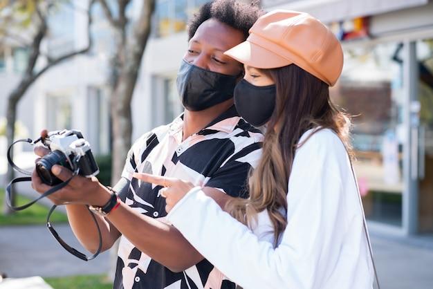 Portrait de jeune couple touristique portant un masque de protection et utilisant un appareil photo tout en prenant des photos dans la ville.