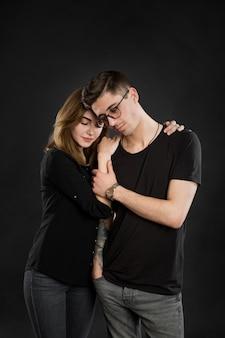 Portrait de jeune couple en vêtements noirs portant des lunettes à la mode et posant sur fond noir.