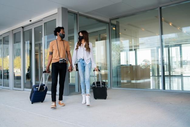 Portrait de jeune couple de voyageurs portant un masque de protection et portant une valise