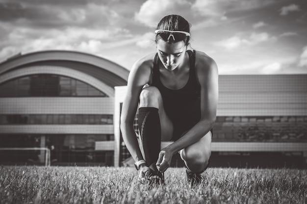 Portrait d'une jeune coureuse qui lace ses bottes dans un stade de football. notion de sport.