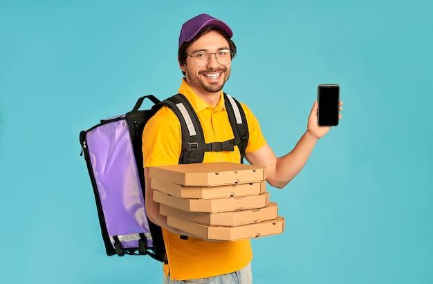 Portrait d'un jeune courrier, livreur de pizza en uniforme avec un sac à dos thermo et montrant un écran de téléphone vide tenant une boîte à pizza isolée. livraison rapide à domicile. commande en ligne.
