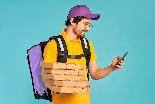 Portrait d'un jeune courrier, livreur de pizza en uniforme avec un sac à dos thermo et un téléphone tenant des boîtes à pizza isolées. livraison rapide à domicile. commande en ligne.