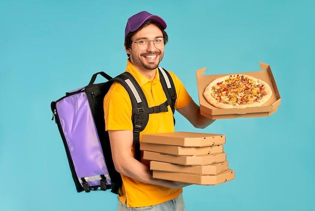 Portrait d'un jeune courrier, livreur de pizza en uniforme avec un sac à dos thermo tenant des boîtes à pizza isolées. livraison rapide à domicile. commande en ligne.