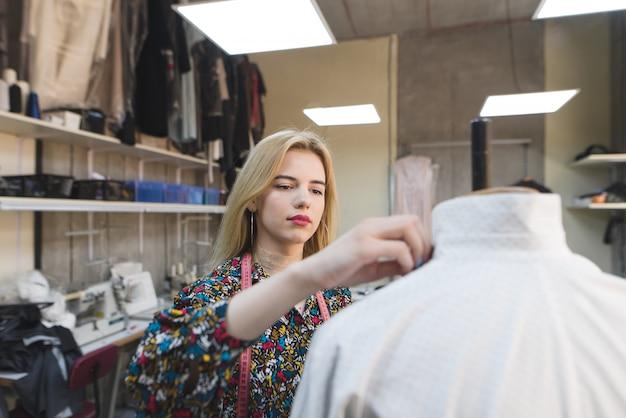 Portrait d'une jeune couturière qui crée des vêtements dans son propre studio de design.