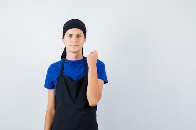 Portrait de jeune cuisinier homme levant le poing fermé en t-shirt, tablier et regardant la vue de face sérieuse