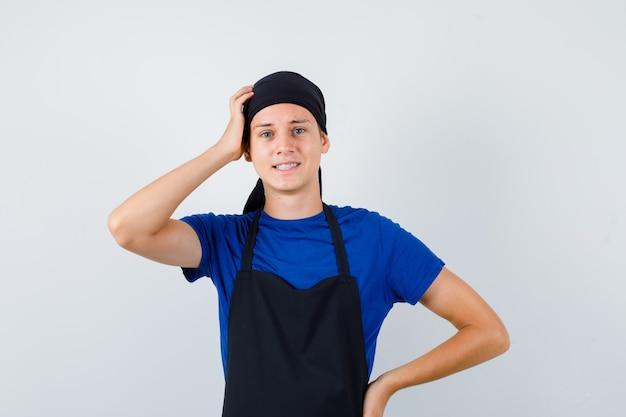 Portrait de jeune cuisinier homme se grattant la tête tout en gardant la main sur la hanche en t-shirt, tablier et regardant pensive vue de face