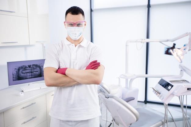 Portrait d'un jeune dentiste en masque de protection, lunettes de travail et en uniforme blanc pendant la quarantaine du coronavirus.