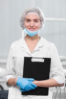 Portrait, jeune, dentiste, tenue, presse-papiers