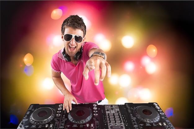 Portrait d'un jeune dj confiant avec un casque sur la tête, mixant de la musique sur une table de mixage