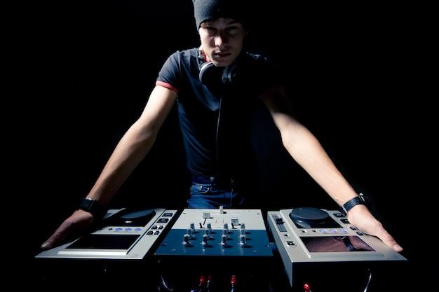 Portrait d'un jeune dj professionnel avec club d'équipement musical dans un éclairage sombre