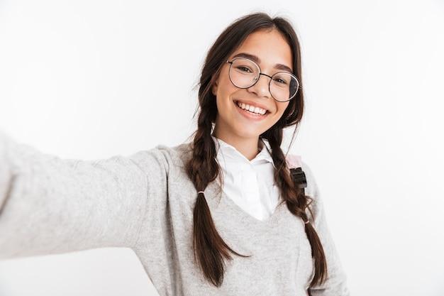 Portrait d'une jeune écolière émotionnelle excitée isolée sur un mur blanc posant prendre un selfie par caméra