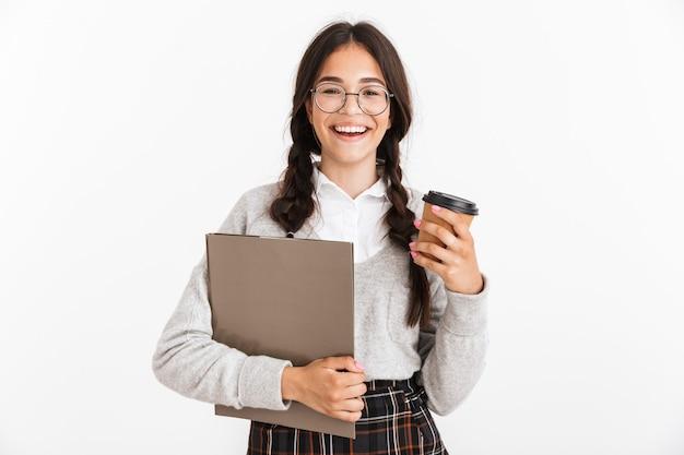 Portrait d'une jeune écolière émotionnelle excitée isolée sur un mur blanc tenant un presse-papiers et du café