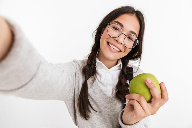 Portrait d'une jeune écolière heureuse isolée sur un mur blanc posant prendre un selfie par caméra manger une pomme