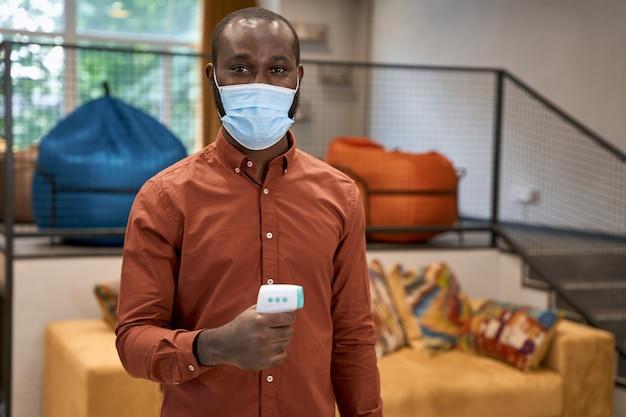 Portrait d'un jeune employé de bureau africain portant un masque de protection médicale tenant un infrarouge