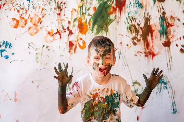 Portrait de jeune enfant heureux jouant avec l'aquarelle. visage d'enfant et vêtements peints au hasard avec des peintures. concept amusant pour les enfants, jeux d'art et hooliganisme. image couleur pour le festival holi. espace de copie