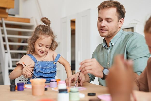 Portrait de jeune enseignant de sexe masculin dessinant des images tout en travaillant avec des enfants à la leçon d'art et d'artisanat dans le centre de développement ou préscolaire