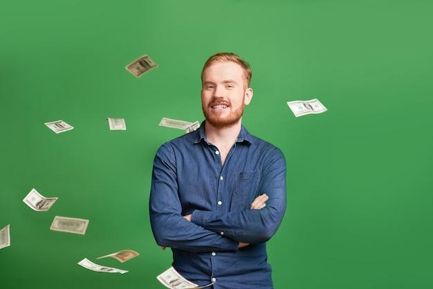 Portrait d'un jeune entrepreneur masculin roux souriant, les bras croisés, debout sous les billets de banque qui tombent
