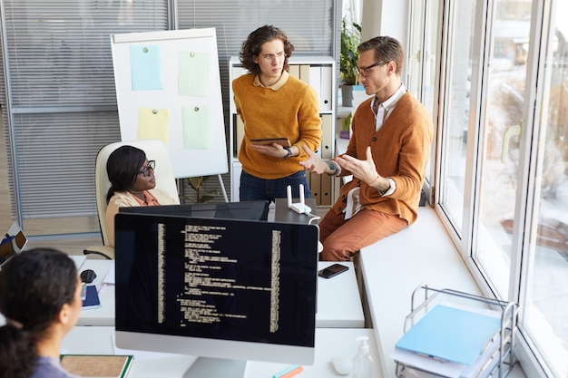 Portrait d'une jeune équipe de développement informatique discutant de la production de logiciels avec du code sur un écran d'ordinateur au premier plan, espace de copie