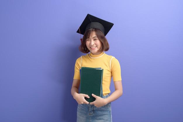 Un portrait de jeune étudiant asiatique portant une casquette de graduation sur fond de studio.