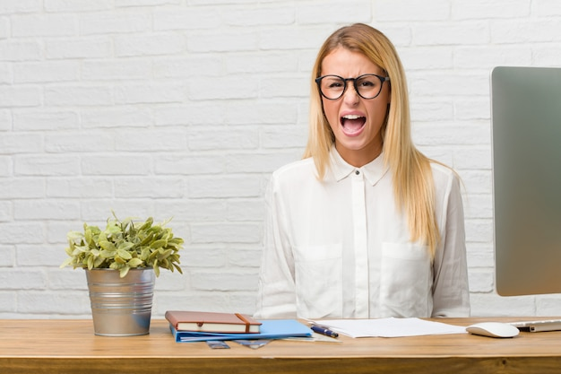 Portrait de jeune étudiant assis sur son bureau à faire des tâches crier en colère.