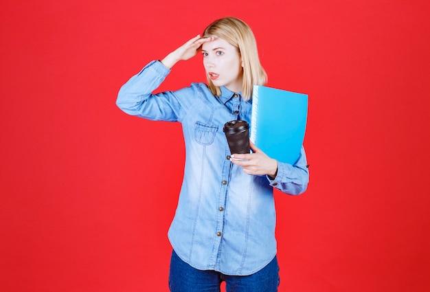 Portrait de jeune étudiant choqué tenant un dossier de document bleu et un café à emporter et à la recherche de quelqu'un