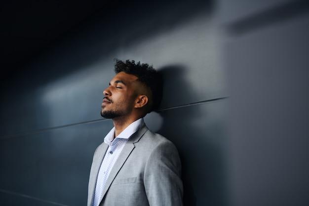 Un portrait d'un jeune étudiant debout à l'extérieur de la ville sur fond noir, les yeux fermés.