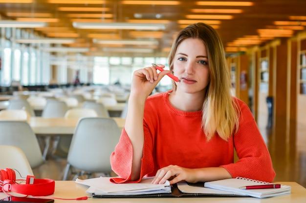 Portrait de jeune étudiant étudiant à la bibliothèque universitaire. concept d'éducation et de style de vie.