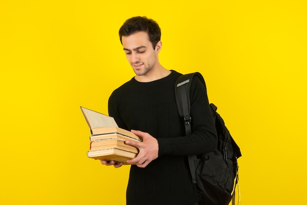 Portrait d'un jeune étudiant lisant des livres sur un mur jaune