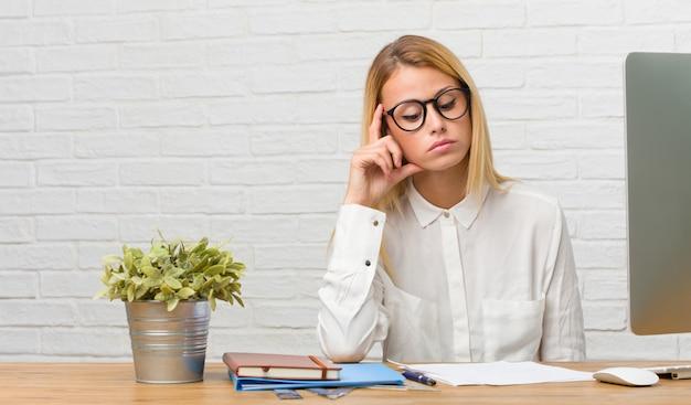 Portrait d'une jeune étudiante assise sur son bureau, effectuant des tâches de réflexion et de recherche, confuse à propos d'une idée, serait en train de chercher une solution