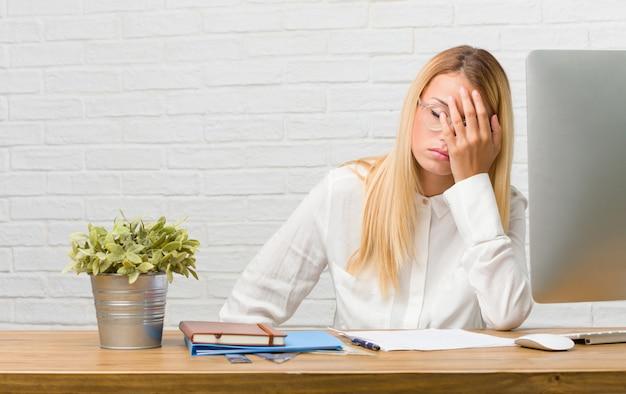 Portrait de jeune étudiante assise sur son bureau à faire des tâches inquiètes et dépassées