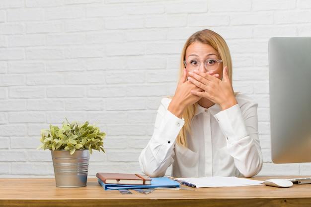 Portrait d'une jeune étudiante assise sur son bureau faisant des tâches couvrant la bouche, symbole de silence et de répression, essayant de ne rien dire
