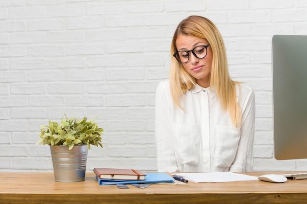 Portrait de jeune étudiante assise sur son bureau faisant des tâches en doutant et haussant les épaules