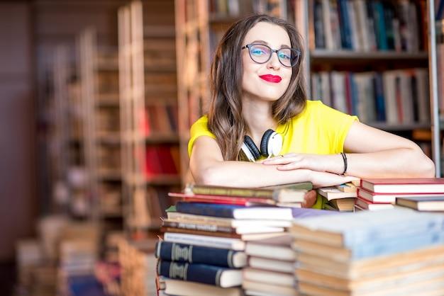 Portrait de jeune étudiante enthousiaste étudiant avec beaucoup de livres à la bibliothèque
