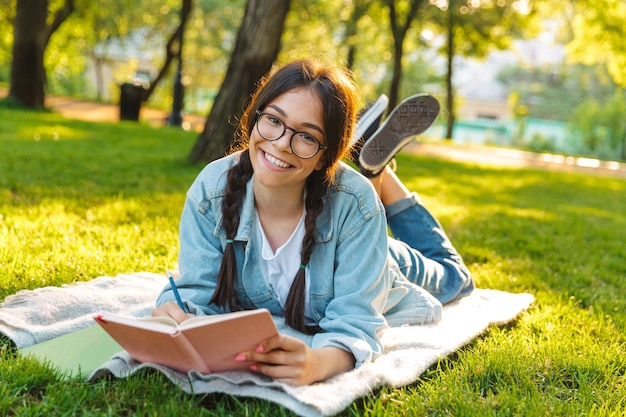 Portrait d'une jeune étudiante heureuse portant des lunettes, assise à l'extérieur dans un parc naturel, écrivant un livre de lecture.