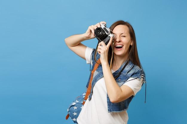 Portrait d'une jeune étudiante joyeuse avec la bouche ouverte avec sac à dos prendre des photos sur un appareil photo vintage rétro isolé sur fond bleu. l'éducation à l'université. copiez l'espace pour la publicité.