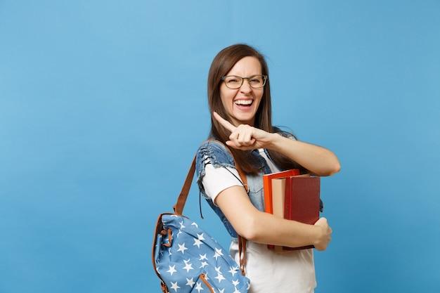 Portrait de jeune étudiante laighing ravie dans des verres avec sac à dos tenant des livres, pointant l'index sur l'espace de copie isolé sur fond bleu. éducation au collège universitaire secondaire.