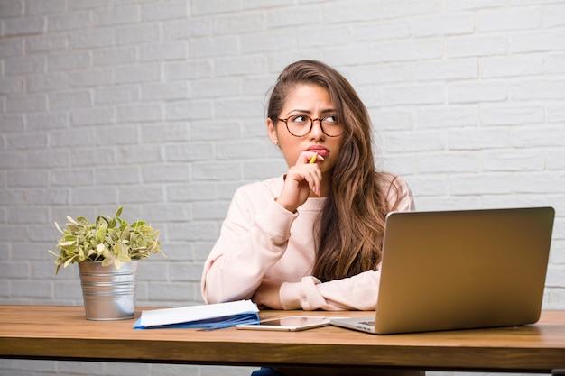 Portrait de jeune étudiante latine femme assise sur son bureau, doutant et confuse, pensant à une idée ou inquiète de quelque chose
