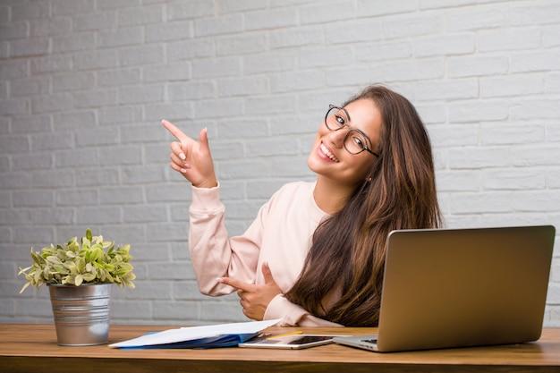 Portrait de jeune étudiante latine femme assise sur son bureau pointant vers le côté