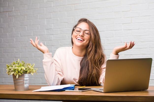 Portrait de jeune étudiante latine femme assise sur son bureau en riant et s'amusant