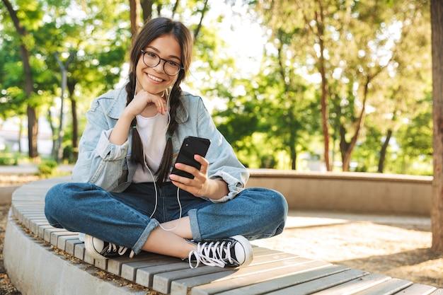 Portrait d'une jeune étudiante mignonne heureuse et heureuse portant des lunettes assise sur un banc à l'extérieur dans un parc naturel à l'aide d'un téléphone portable discutant de la musique avec des écouteurs.