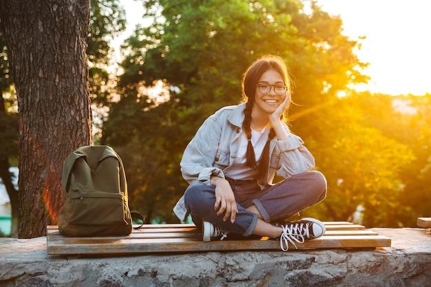 Portrait d'une jeune étudiante mignonne heureuse heureuse portant des lunettes assise sur un banc à l'extérieur dans un parc naturel avec une belle lumière du soleil