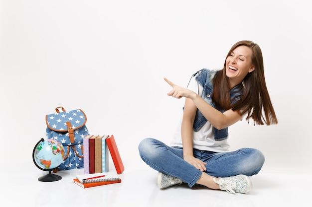 Portrait d'une jeune étudiante riante joyeuse pointant l'index de côté assis près du sac à dos globe, livres scolaires isolés sur mur blanc