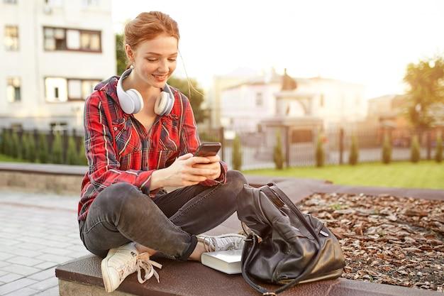Portrait d'une jeune étudiante rousse vêtue d'une chemise à carreaux.