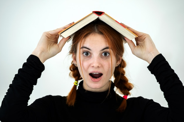 Portrait de jeune étudiante souriante drôle avec un livre ouvert sur la tête. concept de lecture et d'éducation.