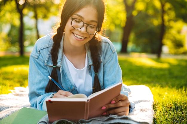 Portrait d'une jeune étudiante souriante portant des lunettes, assise à l'extérieur dans un parc naturel, écrivant un livre de lecture.